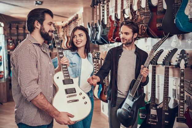 Pareja joven compra nueva guitarra eléctrica en tienda de música