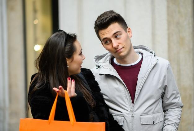 Pareja joven de compras y discutir al aire libre en milán