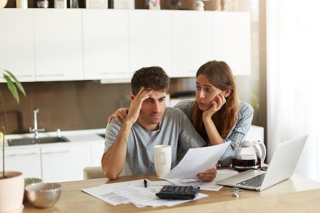 Pareja joven comprobando su presupuesto familiar