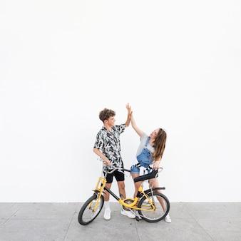 Pareja joven con bicicleta dando alta cinco el uno al otro
