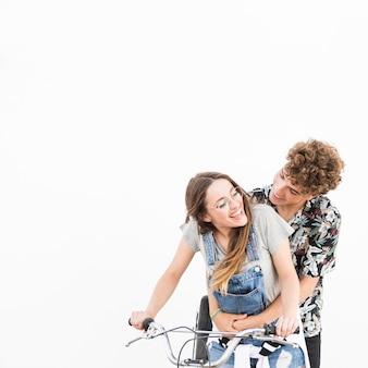 Pareja joven con bicicleta divirtiéndose en el fondo blanco