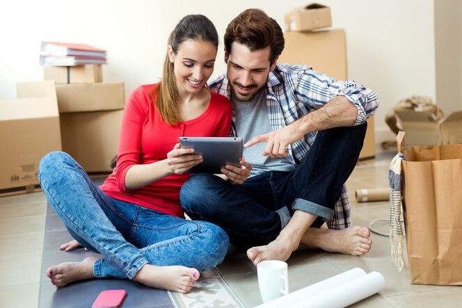 Pareja joven con tableta digital en su nuevo hogar