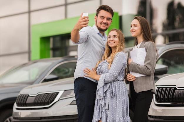 Pareja joven y concesionario de automóviles tomando una selfie