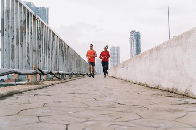 Pareja joven corredor corriendo en la carretera en el parque de la ciudad; deporte, personas, ejercicio y concepto de estilo de vida