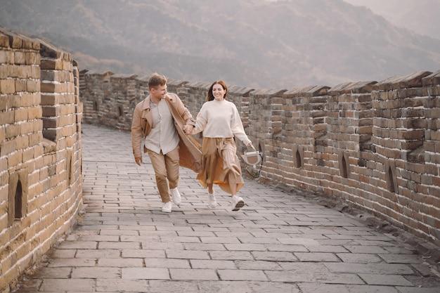 Pareja joven corriendo y girando en la gran muralla china