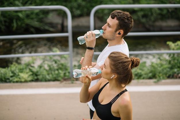 Pareja joven corriendo en el parque de la ciudad con una botella de agua de plástico en las manos, deportes conjuntos, alegría, estilo de vida saludable del deporte de la ciudad, fitness juntos, noche de verano, corredores, agua potable, sed