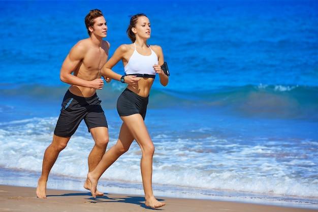 Pareja joven corriendo en la playa en verano