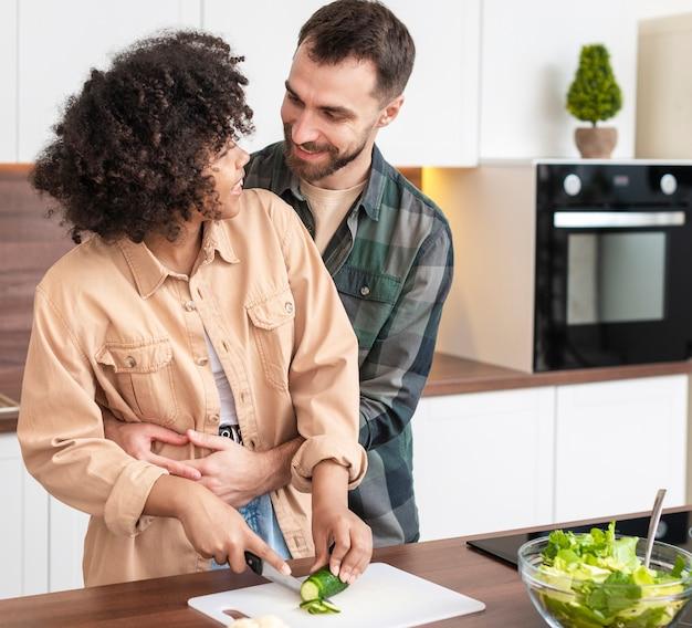 Pareja joven cortando verduras juntos