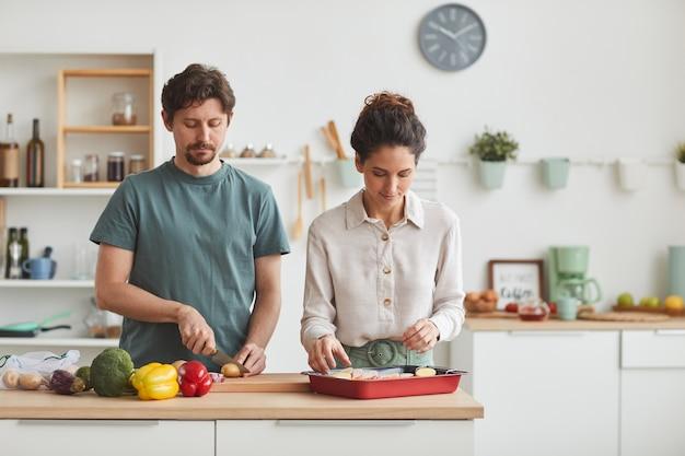 Pareja joven cortando verduras en la mesa y preparando la cena juntos en la cocina de casa