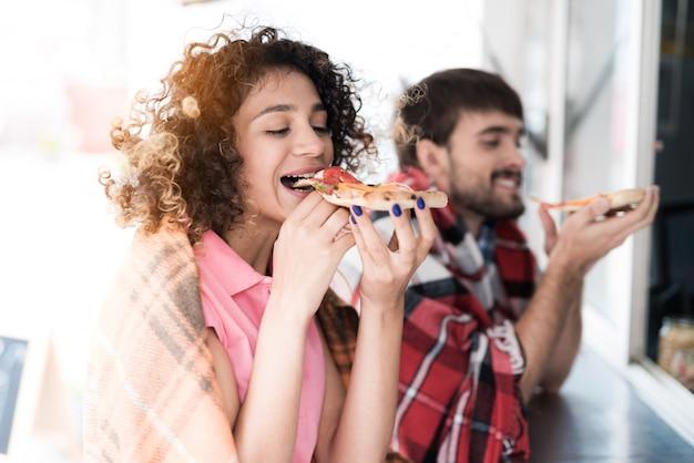 Pareja joven en cuadros cuadros comiendo pizza.