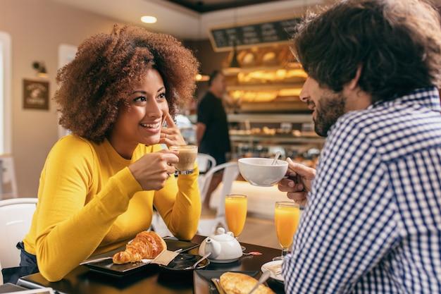Pareja joven desayunando en la cafetería, tomando té y jugo de naranja, comiendo un croissant