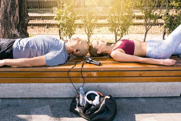 Pareja joven descansando en un banco con equipo deportivo en el parque