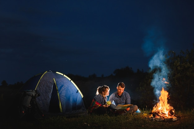 Pareja joven descansando en la hoguera junto al campamento y la carpa turística azul, bebiendo té, disfrutando del cielo nocturno