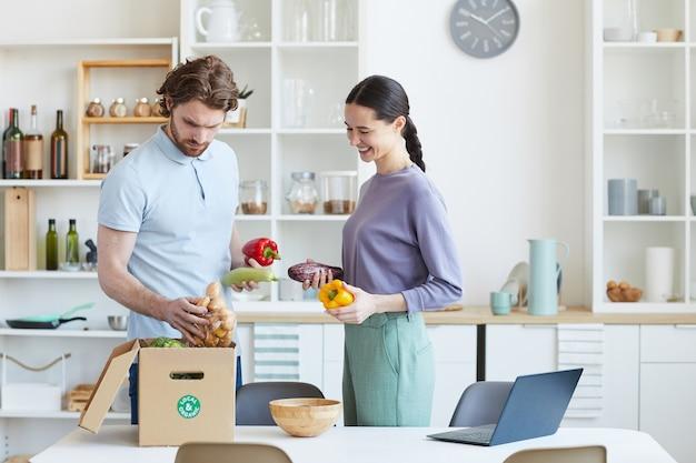 Pareja joven desembalaje de alimentos juntos de la caja de cartón después de comprar