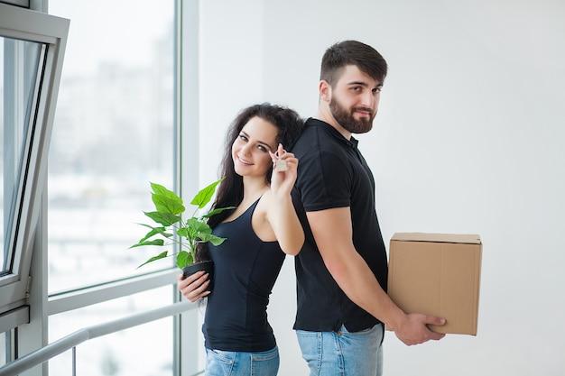 Pareja joven desempacando cajas de cartón en casa nueva
