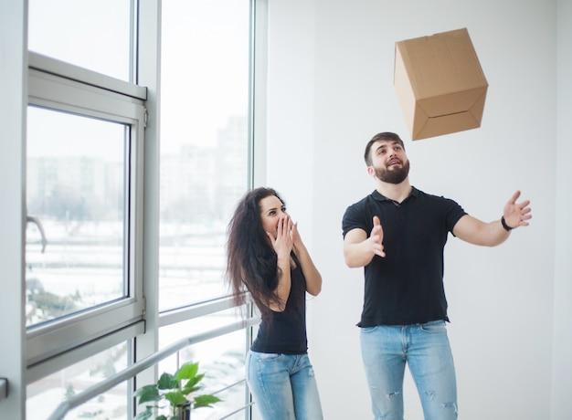 Pareja joven desempacando cajas de cartón en su nuevo hogar