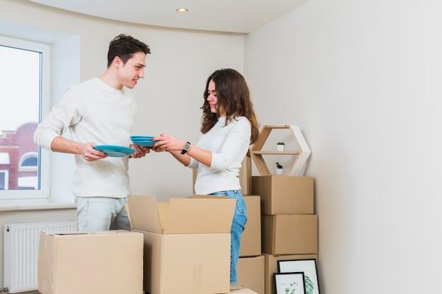 Pareja joven desempacando los platos azules de cajas de cartón en su nueva casa