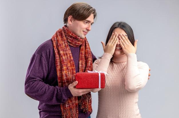 Pareja joven en el día de san valentín chico complacido dando caja de regalo a chica aislada sobre fondo blanco.