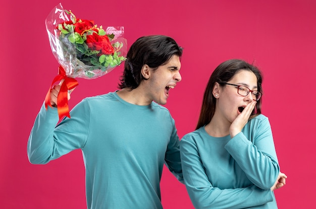Pareja joven en el día de san valentín chico enojado levantando ramo chica cubrió la boca con la mano aislada sobre fondo rosa
