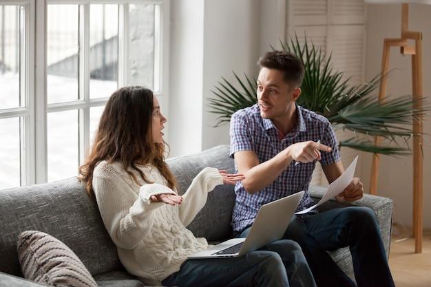 Pareja joven discutiendo sobre facturas altas con computadora portátil y documentos