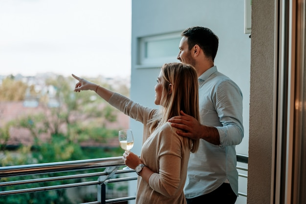 Pareja joven disfruta de beber vino en el balcón. mujer apuntando a algo.