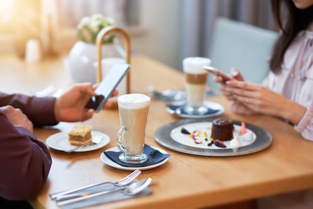 Pareja joven disfrutando de un café y un pastel en el café