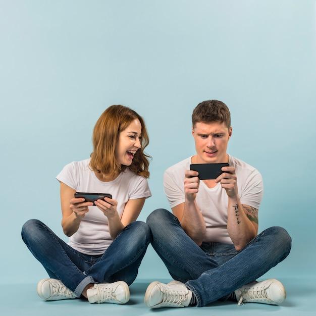 Pareja joven disfrutando del videojuego en el teléfono móvil contra el fondo azul
