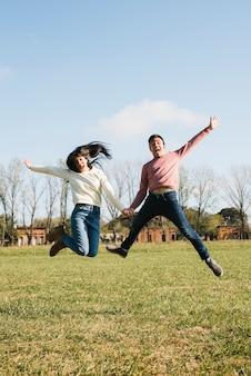 Pareja joven divertida saltando en el campo tomados de la mano