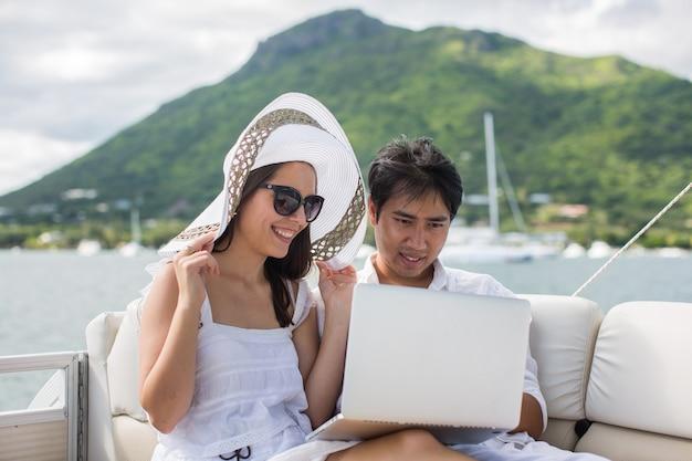 Pareja joven divirtiéndose en el barco con un portátil