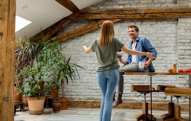 Pareja joven divirtiéndose juntos en la cocina rústica Foto Premium