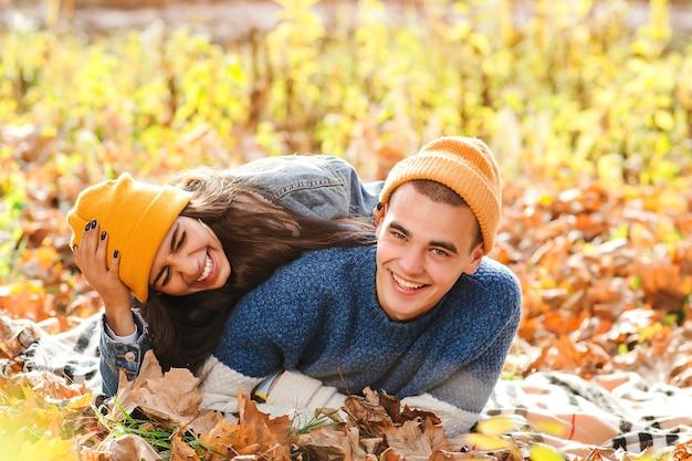 Pareja joven divirtiéndose juntos en otoño. amor. pareja de moda disfrutando del otoño. moda, estilo de vida y vacaciones de otoño. elegante hombre y mujer entre hojas de otoño.