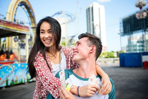 Pareja joven divirtiéndose juntos en un parque de diversiones