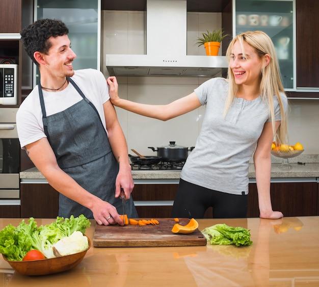 Pareja joven divirtiéndose mientras corta verduras en la cocina