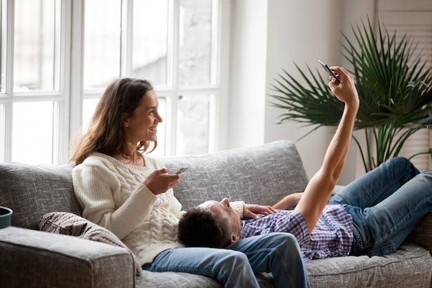 Pareja joven divirtiéndose con smartphones tomando selfie en casa