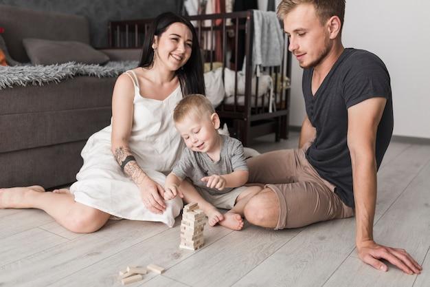 Pareja joven divirtiéndose con su pequeño hijo jugando con bloques de madera