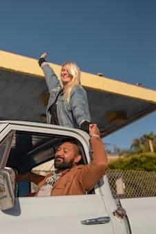 Pareja joven divirtiéndose en su viaje en coche con una mujer en el maletero trasero
