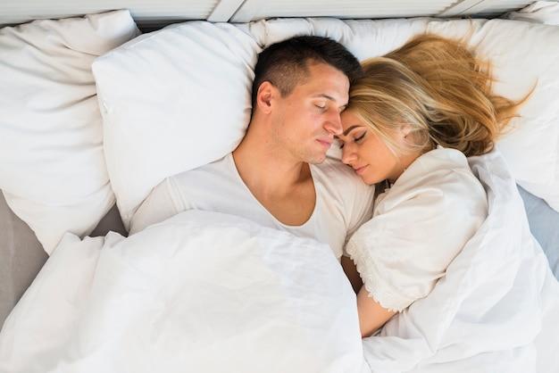 Pareja joven durmiendo debajo de la manta en la cama