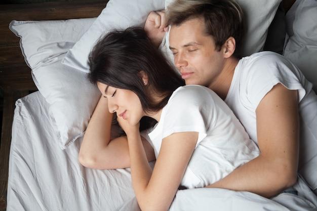 Pareja joven durmiendo juntos abrazando acostado dormido en una cama cómoda