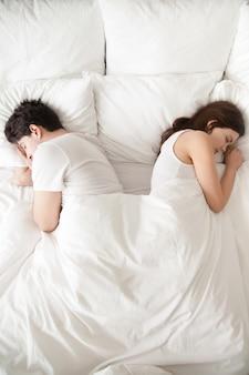 Pareja joven durmiendo por separado en la cama, espalda con espalda, vertical.