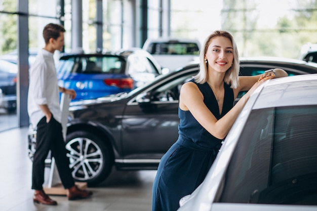 Pareja joven eligiendo un automóvil en una sala de exhibición de autos
