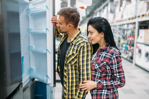 Pareja joven eligiendo refrigerador en supermercado. clientes masculinos y femeninos en compras familiares. hombre y mujer comprando bienes para la casa.