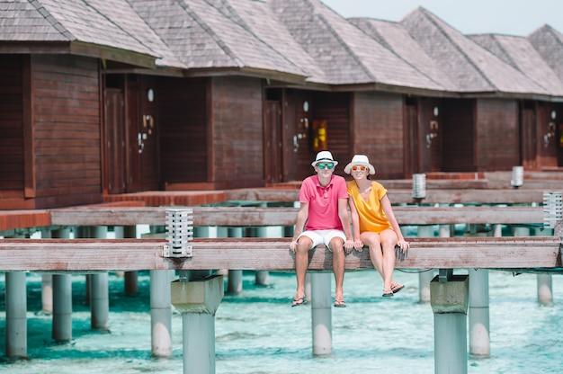 Pareja joven en el embarcadero de la playa en una isla tropical en luna de miel