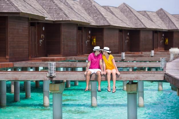 Pareja joven en el embarcadero de playa tropical cerca de bungalow de agua