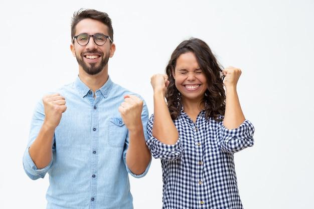 Pareja joven emocionada celebrando el éxito
