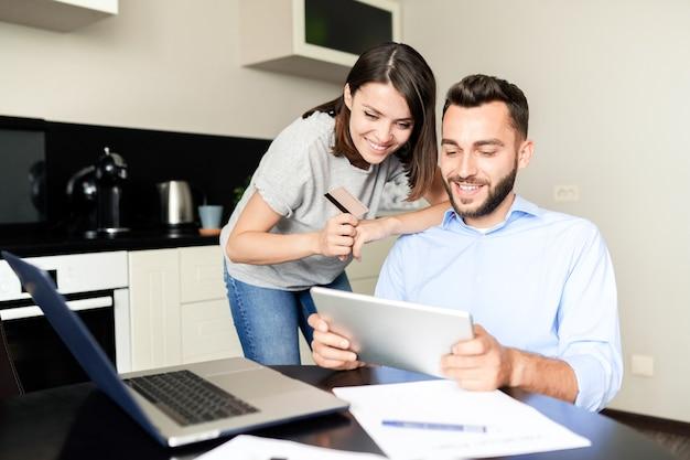 Pareja joven emocionada positiva usando tableta digital mientras elige productos en la tienda de internet juntos en la cocina