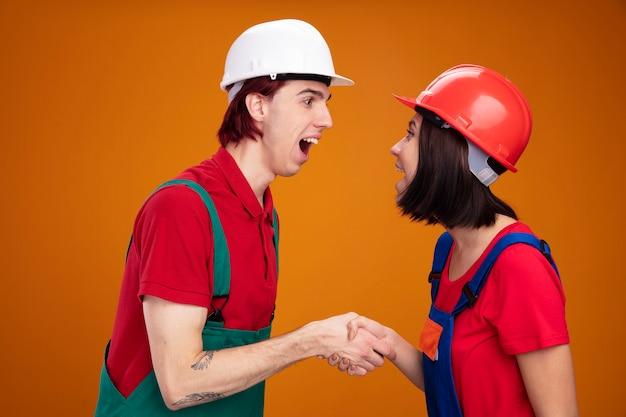 Pareja joven emocionada en uniforme de trabajador de la construcción y casco de seguridad de pie en vista de perfil mirando el uno al otro tomados de la mano aislados en la pared naranja