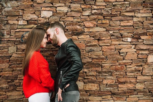 Pareja joven enamorada enfrente de muro de ladrillo