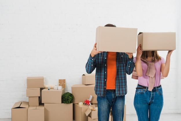 Pareja joven escondiendo sus caras con cajas de cartón en casa nueva