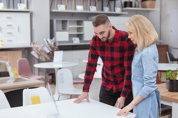 Pareja joven examinando mesas a la venta en la tienda de muebles