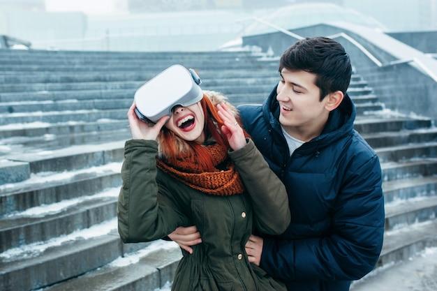 Pareja joven experimentando realidad virtual (vr) en la calle